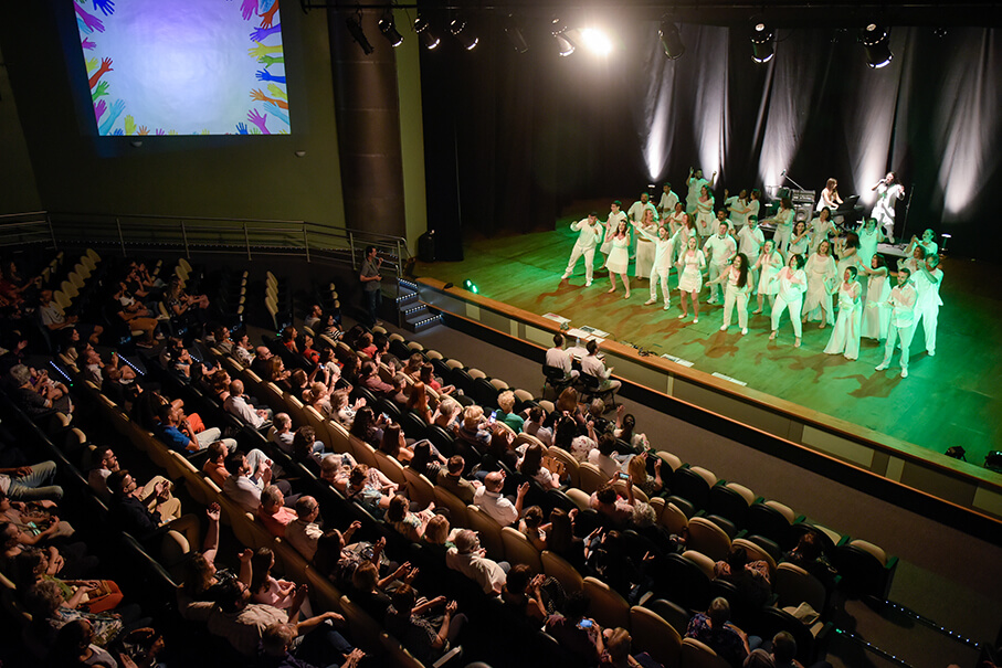 Vista superior do palco e da plateia. Coristas se apresentam e público assiste.