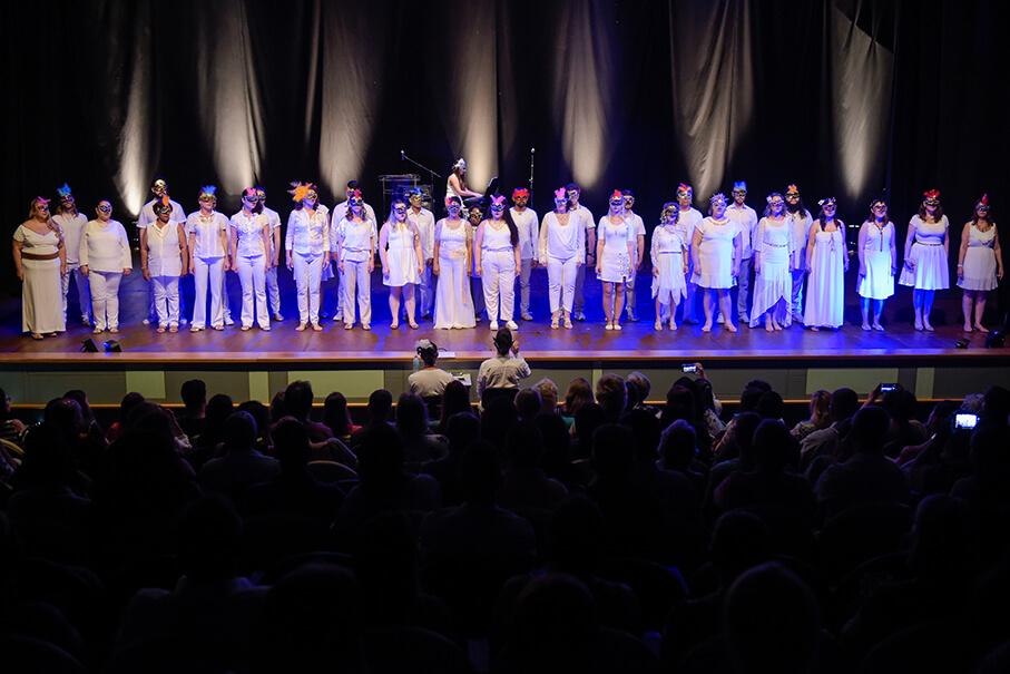 Coral da PUCRS reunido no palco, vestidos de branco, apresentando a peça.