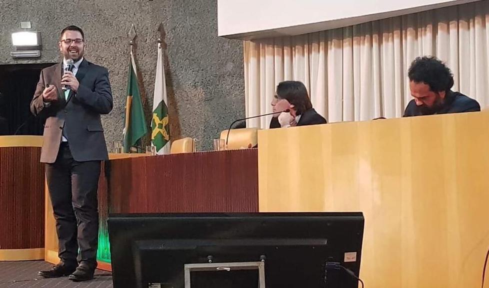 Pesquisador Rodrigo Grassi-Oliveria, em pé, com microfone na mão, junto a uma bancada de madeira, apresenta pesquisa sobre crack